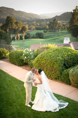 Bride and groom kiss on lawn with golf course view