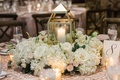white lit candle in lantern with white flowers centerpiece