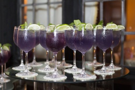 Wedding reception with a display of violet drinks, limes in stemmed glassware