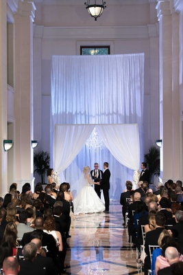 Bride in an Ines Di Santo dress with groom in black tux under fabric chuppah with crystal chandelier