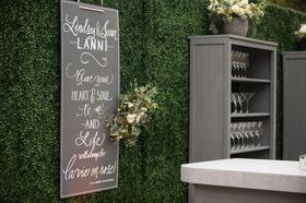 Outdoor wedding green boxwood hedge wall chalkboard sign Louis Armstrong quote grey bookshelf bar