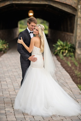 Bride in white strapless dress with groom in tuxedo
