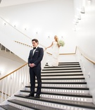 bride walking down steps groom first look modern wedding dress tuxedo museum contemporary art