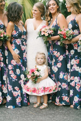 bride in v neck wedding dress bridesmaids in navy floral bridesmaid dresses flower girl flower dress