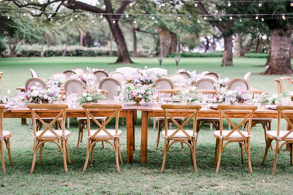 wedding reception outdoor hawaii string lights long wood table vineyard chairs low centerpieces