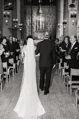 black and white photo of father walking bride down the aisle from the back