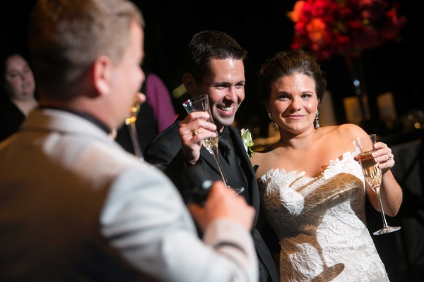 a bride and groom raise their Champagne glasses in toast during the reception