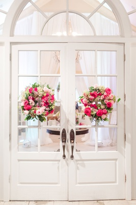 wedding reception entrance white doors with pink rose wreaths greenery flowers