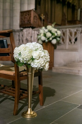 Gold trumpet vase with arrangement of white roses and hydrangeas at ceremony