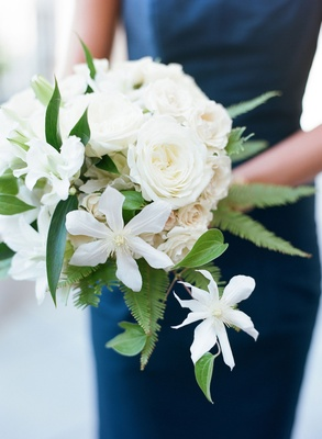 Bridesmaids wearing navy blue dresses holding bouquets of roses, greenery, and ferns fern