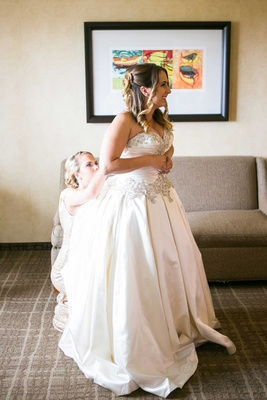 bride in allure ball gown helped into dress by bridesmaid and little sister