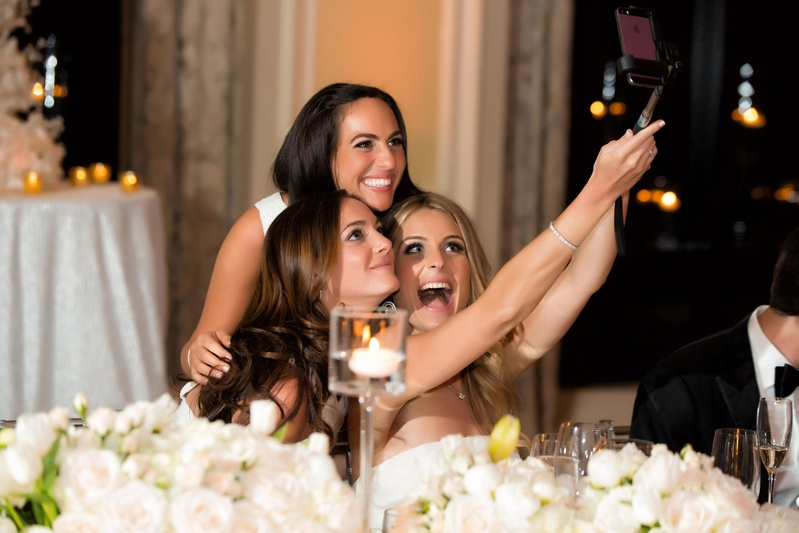 Bride sitting down at reception taking selfie with bridesmaids on selfie stick