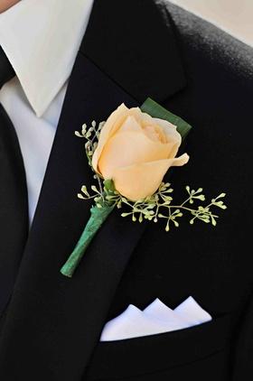 Single ivory rose on black tuxedo lapel