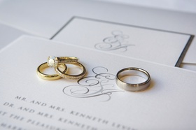 Platinum men's band and gold diamond rings on invite