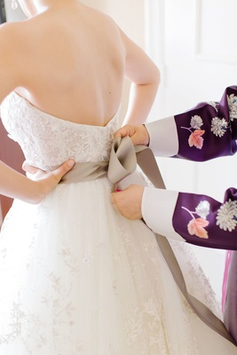 tying bow on wedding dress