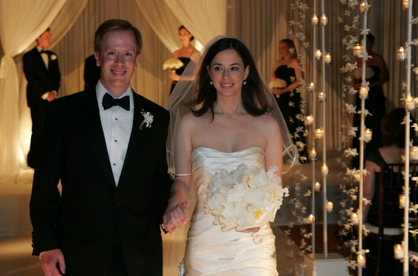 Bride in a veil and strapless gown and groom in a black tuxedo