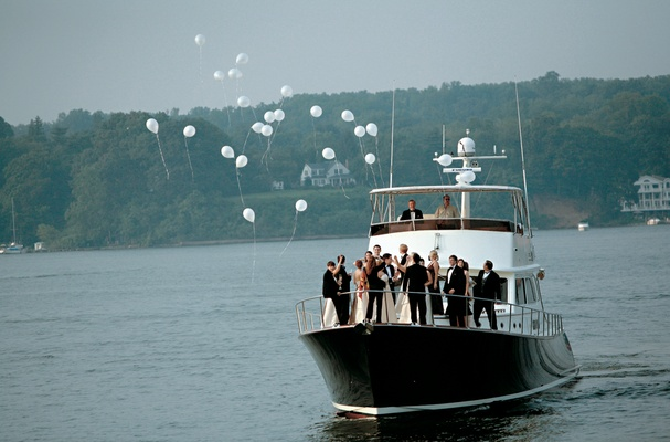 wedding party releases balloons on boat ride around river