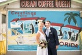 Bride and groom taking portrait in front of Cuban coffee store with post card greeting mural on wall