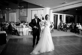 black and white photo of father of the bride dances with his daughter in a winnie couture gown
