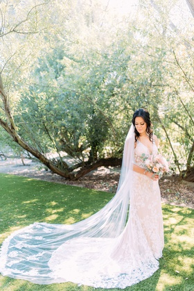 bride in calla blanche wedding dress train bouquet muted color palette long cathedral veil