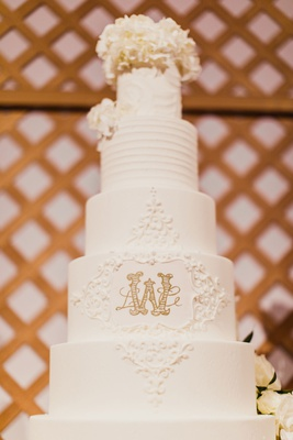 tall wedding cake with ivory flower topper and gold monogram design