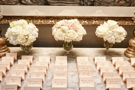beige place cards with black calligraphy and cream and blush bouquets