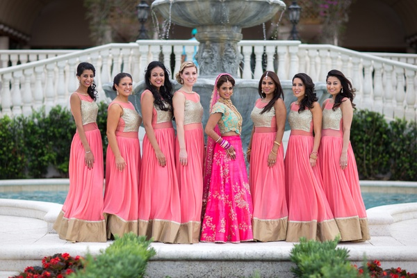 Indian-American bride in pink and turquoise lehenga, bridesmaids in traditional outfit in pink, tan
