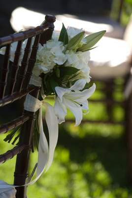 White flower arrangement tied to ceremony chair