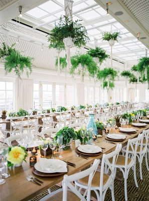Wedding reception long table wood with white chairs ferns from ceiling low arrangements of flowers