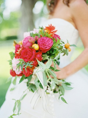 Bride holding bright wedding bouquet with greenery, red flowers, pink flowers, and fruit