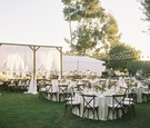 outdoor reception with bistro lights, canopy over head tables, vineyard chairs