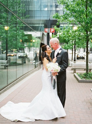 newlyweds stare into each others eyes full wedding attire dress long train charcoal tuxedo bouquet