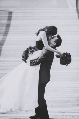Black and white photo of groom picking up bride