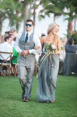 Garden wedding with bridesmaid in strapless light grey dress, protea, greenery bouquet, groomsman