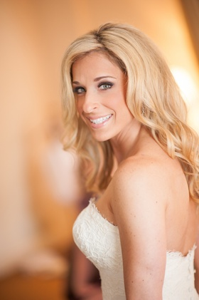 Bride in a strapless lace Isabelle Armstrong dress with loose curls and subtle makeup