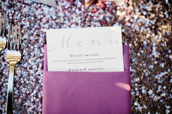 Wedding reception sit-down dinner menu in purple napkin on sequined tablecloth