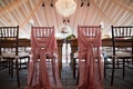sheer pink fabric tied around the reception chairs for both the bride and the groom