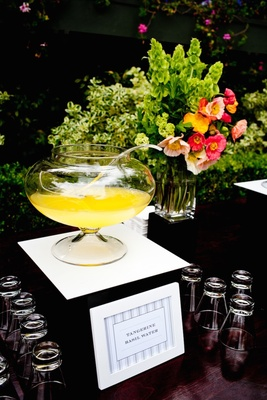 Yellow drink in punch bowl with sign at wedding