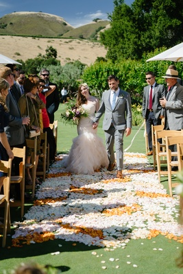 bride in blush ruffled mermaid dress walks down the aisle with groom in grey suit and sky blue tie