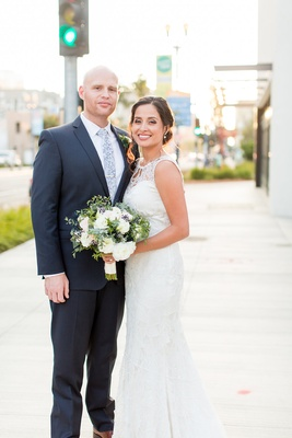 Wedding portrait on street sidewalk in Long Beach bride in Claire Pettibone wedding dress groom suit