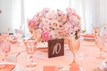 Pink bridal shower decor with rose, ranunculus, hydrangea flower arrangement pink glassware coupe