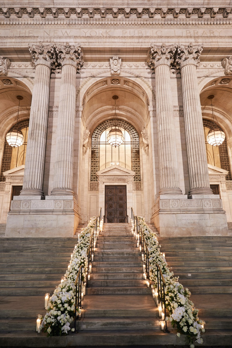 staircase to new york public library wedding reception venue white flowers greenery on stair railing