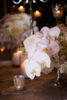 Wedding reception table with white orchids, hydrangeas in a silver stand