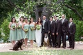 Bride in a Claire Pettibone gown with groom and bridal party in a garden