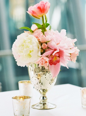 small floral arrangement pink white and greenery in gold vase small candles white table linen