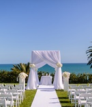 white chuppah, chuppah with white cloth and white flowers