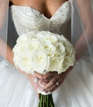 Bride in Ines Di Santo beaded wedding dress with ivory rose bouquet