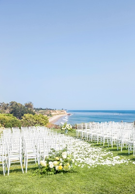 wedding ceremony on grass bluff overlooking pacific ocean beach white chair yellow flowers sunny