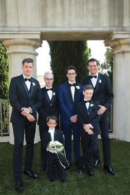 groom in navy tuxedo, groomsmen in black tuxedo, junior groomsman, ring bearer with white tie