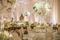 Wedding reception ballroom drapery flowers hanging from ceiling white centerpiece rose gold chair